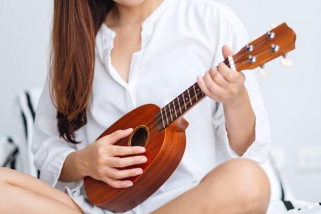 Zbliżenie wizerunek kobiety obsiadanie i bawić się ukulele w sypialni