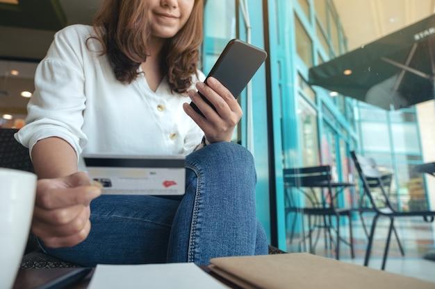 Zbliżenie wizerunek kobiety posiadającej kartę kredytową i korzystania z bankowości mobilnej, siedząc w kawiarni