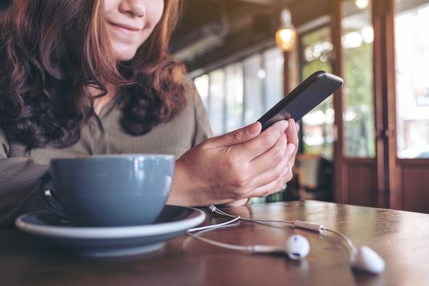 Zbliżenie wizerunek kobiety przy użyciu telefonu komórkowego podczas słuchania muzyki w słuchawkach i filiżankę kawy na drewnianym stole w kawiarni