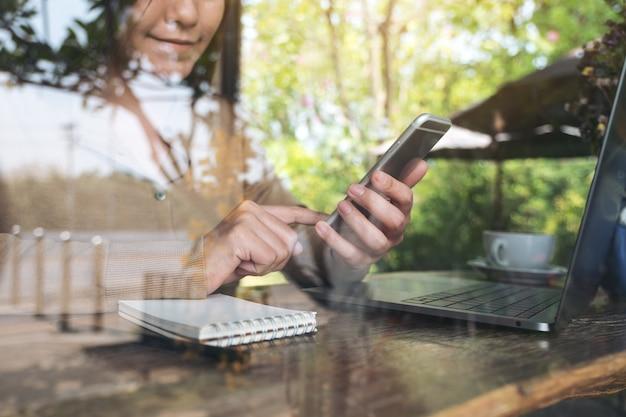 Zbliżenie wizerunek kobiety ręki mienie i patrzeć mądrze telefon podczas gdy używać laptop