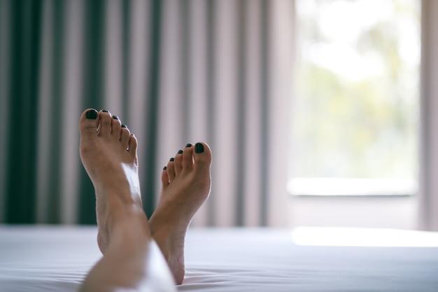Zbliżenie wizerunek kobiety stóp na białym łóżku