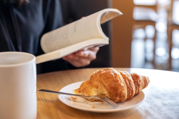 Zbliżenie wizerunek kobiety trzymającej i czytającej książkę z kawałkiem rogalika na talerzu i filiżanką kawy na drewnianym stole