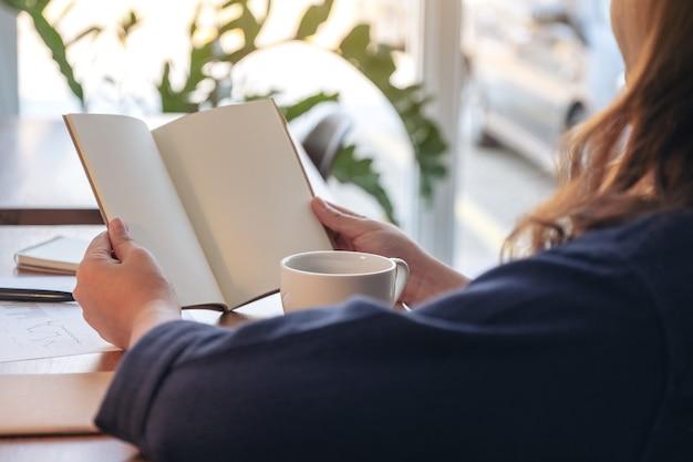 Zbliżenie wizerunek kobiety trzymającej i otwierając pusty notatnik z filiżanką kawy i papierami na stole