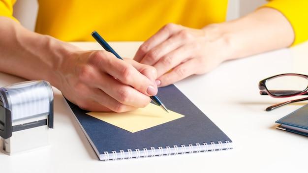 Zbliżenie wizerunek kobiety zapisywanie na żółtej karcie papieru
