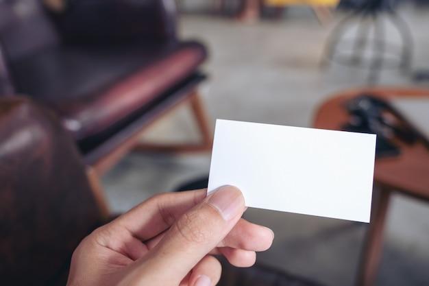 Zbliżenie wizerunek mężczyzna ręki mienia pusta wizytówka w kawiarni