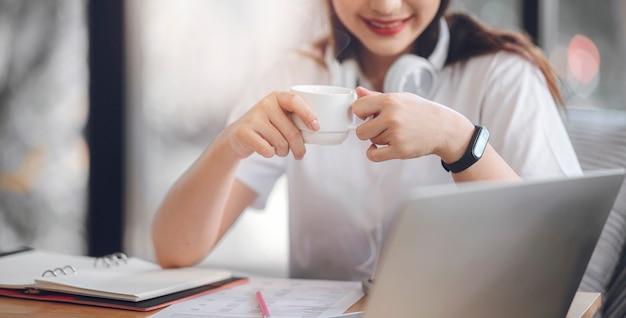 Zbliżenie wizerunek młoda atrakcyjna kobieta pije kawę podczas gdy pracujący z laptopem w domu.