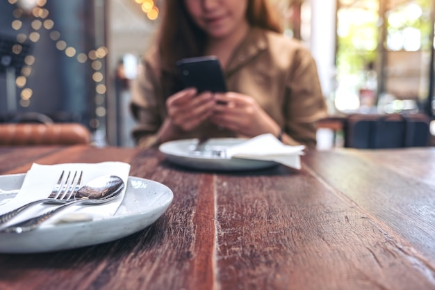 Zbliżenie wizerunek pięknej kobiety trzymając, używając i patrząc na inteligentny telefon jedząc posiłek w restauracji