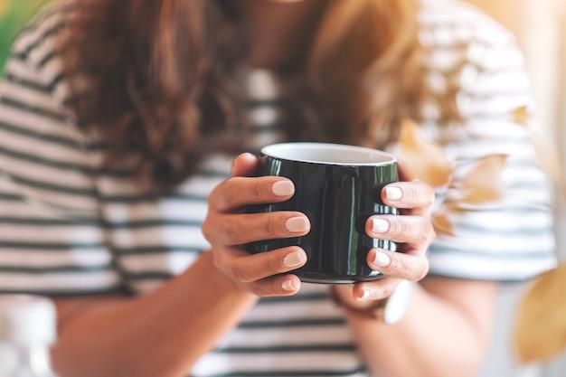 Zbliżenie wizerunek pięknej kobiety trzymającej czarną filiżankę gorącej kawy do picia