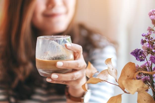 Zbliżenie wizerunek pięknej kobiety trzymającej szklankę mrożonej kawy do picia w kawiarni