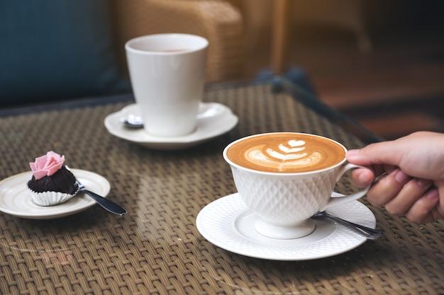 Zbliżenie wizerunek ręka trzyma filiżankę gorąca latte kawa z latte sztuką i przekąską