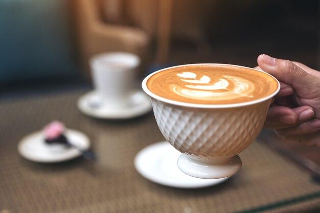 Zbliżenie wizerunek ręka trzyma filiżankę gorąca latte kawa z latte sztuką w kawiarni
