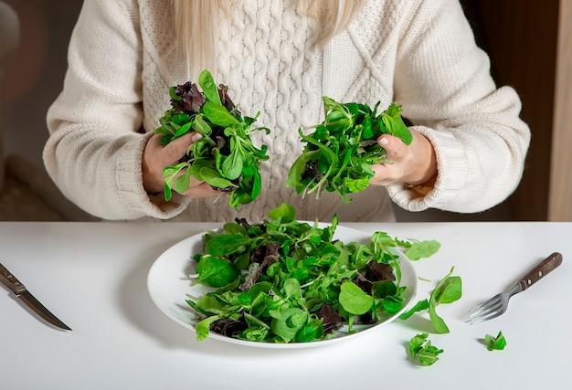 Zbliżenie: woaman ręce trzymając zielone liście sałaty