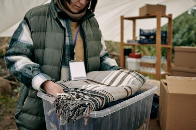 Zbliżenie wolontariuszki z odznaką pakującą rzeczy do pojemnika podczas przygotowywania ciepłego koca dla uchodźców