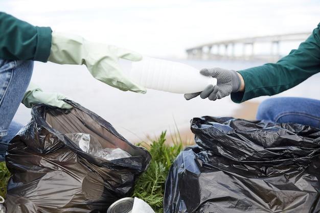 Zbliżenie wolontariuszy sprzątających przyrodę ze śmieci, które wkładają plastikowe butelki do worków na śmieci