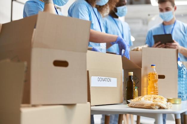 Zbliżenie wolontariuszy z pudełek darowizn w ochronnych maskach i rękawiczkach, sortujących i pakujących żywność