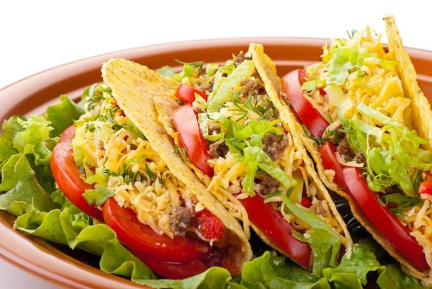 Zbliżenie wołowiny tacos podawanej z salsą sałatką i świeżymi pomidorami na białym tle
