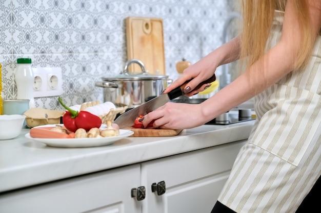 Zbliżenie: womans ręce przygotowujące jedzenie w kuchni, krojenie papryki nożem, na desce do krojenia
