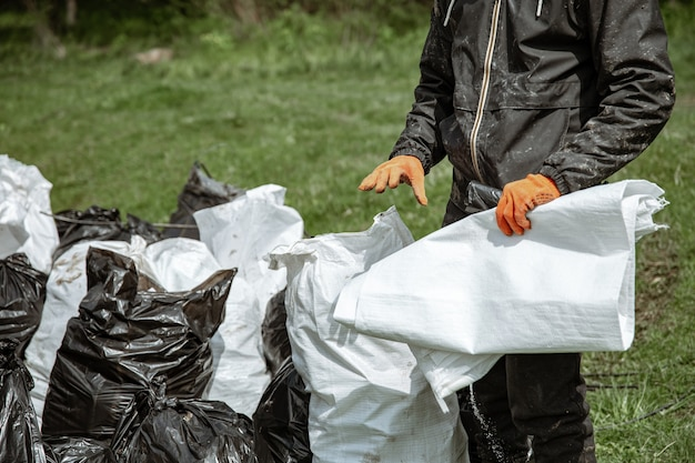 Zbliżenie worków na śmieci wypełnionych śmieciami po oczyszczeniu środowiska.