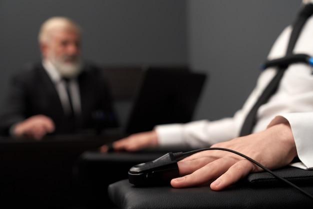 Zbliżenie wskaźnika pulsu na ręce podczas testu wykrywacza kłamstw