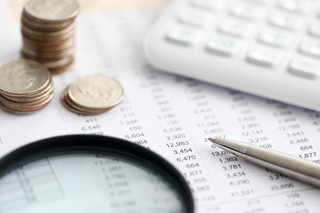 Zbliżenie wyciągu bankowego, kalkulatora, stosu monet i pióra. raport pracownika banku