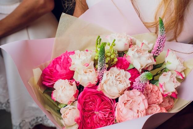 Zbliżenie wyciszony bukiet ślubny z różowe i fioletowe kwiaty.