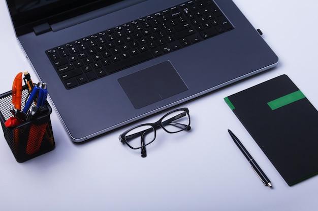 Zbliżenie wygodne miejsce pracy w biurze z laptopem, myszą, notebookiem, okularami, piórem i innym sprzętem