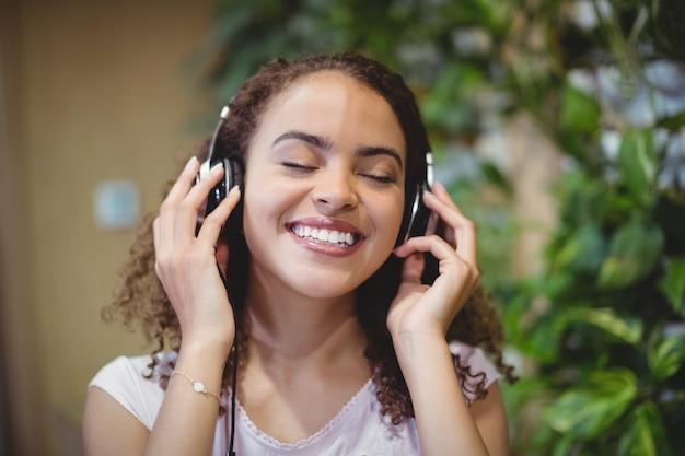 Zbliżenie: wykonawczy żeński biznes słuchania muzyki na słuchawkach