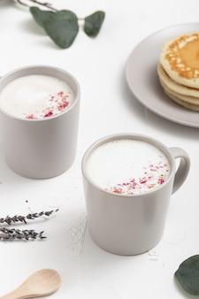 Zbliżenie wysoki kąt strzału filiżanki kawy i niektóre dekoracje na białym stole