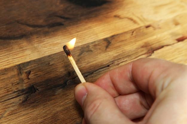 Zbliżenie wysoki kąt strzału osoby posiadającej płonącą zapałkę na powierzchni drewnianych