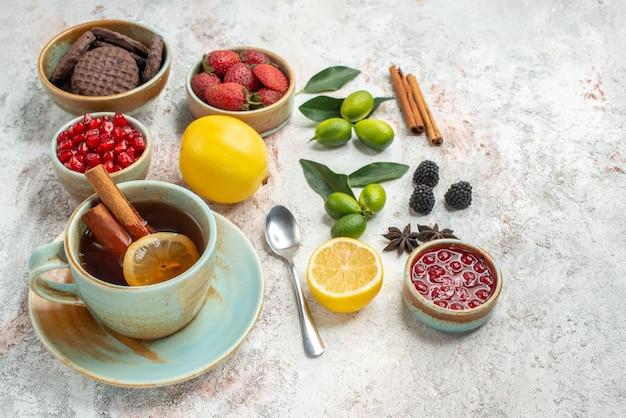 Zbliżenie z boku ciasteczka i jagody cynamon apetyczne ciasteczka truskawki pestki granatu łyżka cytryny filiżanka herbaty owoce cytrusowe na stole
