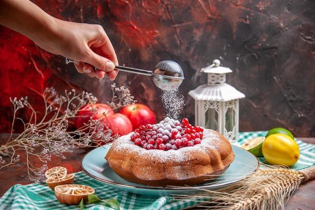 Zbliżenie z boku ciasto owoce cytrusowe ciasto z jagodami jabłka łyżka w dłoni