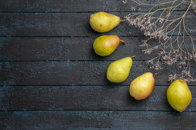 Zbliżenie z boku pięć gruszek pięć zielonych gruszek po prawej stronie ciemnego stołu obok gałęzi drzew