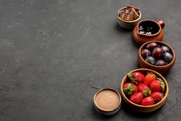 Zbliżenie z boku sos czekoladowy jagody truskawki sos czekoladowy i jagody w miskach po prawej stronie ciemnego stołu