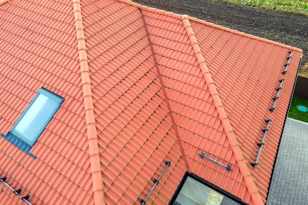 Zbliżenie z cegły dach domu z żółtą pokrywą gontów i szklanych okien na poddaszu.