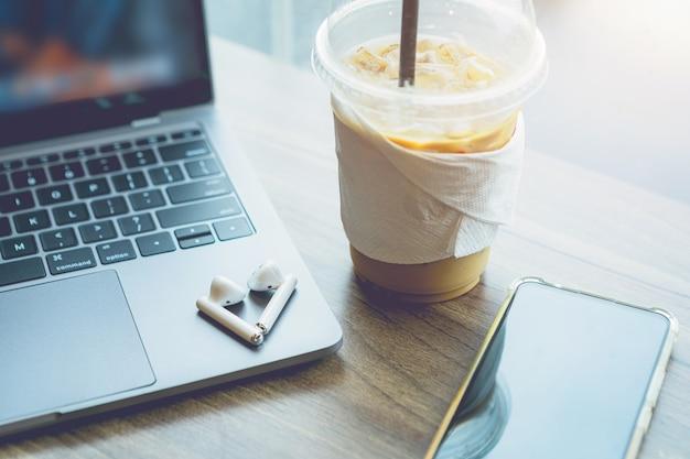 Zbliżenie z filiżanką kawy pracy z laptopem i słuchawką, smartfon z izolacją na drewnianym biurku w kawiarni jak tło