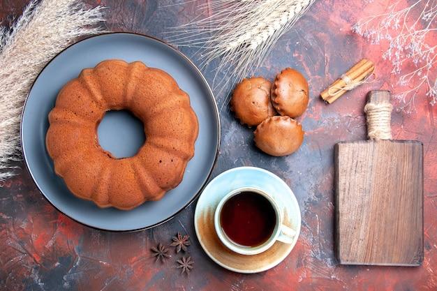 Zbliżenie z góry apetyczne ciasto ciasto babeczki filiżanka herbaty drewniana deska do krojenia pszenne kłosy