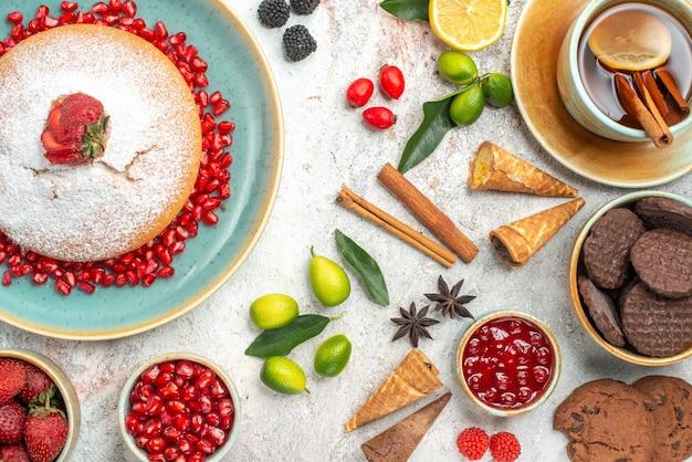 Zbliżenie z góry ciasteczka i ciasto ciasteczka filiżanka herbaty owoce cytrusowe laski cynamonu