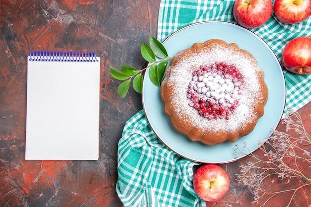 Zbliżenie z góry ciasto biały notatnik ciasto z czerwonymi porzeczkami jabłka na obrusie w kratkę