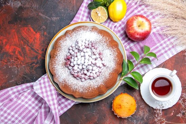 Zbliżenie z góry ciasto ciasto filiżanka herbaty owoce cytrusowe na obrusie liście jabłka