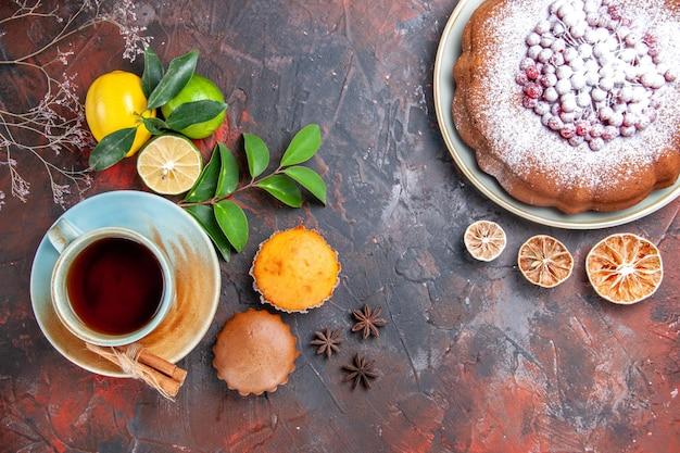 Zbliżenie z góry filiżanka herbaty babeczki filiżanka herbaty cynamon owoce cytrusowe ciasto anyż gwiazdkowaty
