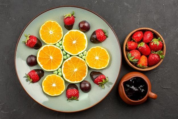 Zbliżenie z góry pomarańczowe i czekoladowe miski sosu czekoladowego i truskawek oraz talerz posiekanych pomarańczowych, truskawkowych zielonych cukierków w czekoladzie na środku ciemnego stołu