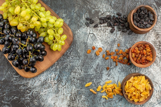 Zbliżenie z góry suszone owoce apetyczne winogrona na desce suszone owoce w brązowych miseczkach