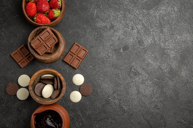 Zbliżenie z góry truskawki i czekoladowe truskawki sos czekoladowo-czekoladowy w miseczkach po lewej stronie stołu