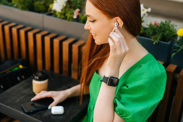 Zbliżenie z góry uśmiechnięta młoda kobieta dotykająca bezprzewodowych słuchawek, słuchanie muzyki za pomocą telefonu komórkowego siedzącego przy stole, na tarasie kawiarni na świeżym powietrzu w letni dzień, rozmyte tło, selektywne focus