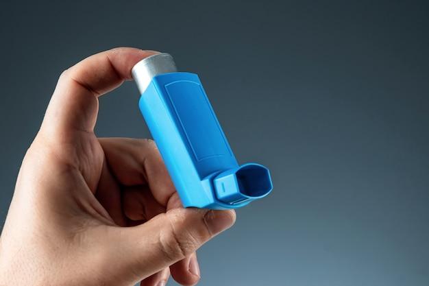 Zbliżenie z inhalatorem astmy w męskiej dłoni, atak astmatyczny. pojęcie leczenia astmy oskrzelowej, kaszlu, alergii, duszności.