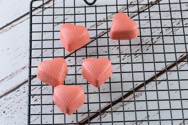 Zbliżenie z kilku białych czekoladek podbarwionych różową farbą, na czarnej poręczy