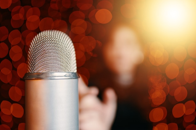 Zbliżenie z kopią przestrzeni mikrofonu w sali koncertowej retro mikrofon na scenie i sylwetka kobiety w b...