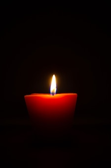 Zbliżenie z płonącą świecą na białym tle na czarnym tle.
