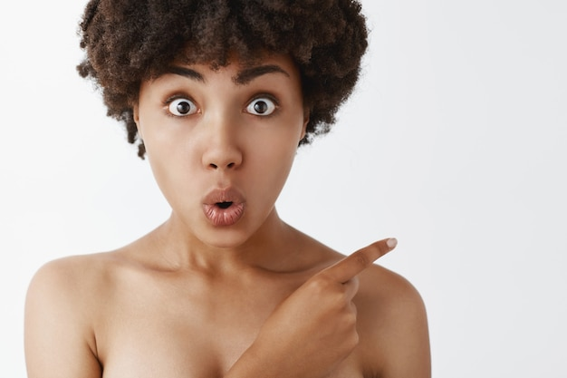 Zbliżenie z pod wrażeniem zaintrygowanej i zainteresowanej atrakcyjnej młodej afroamerykanki z fryzurą afro skierowaną w prawy górny róg, składającą usta z ciekawości i zdumienia, pozującą nago