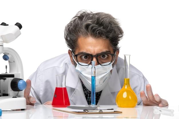 Zbliżenie z przodu naukowiec w średnim wieku w specjalnym garniturze siedzący z roztworami i patrząc na nie na białym tle męski wirus nauka covid chemia